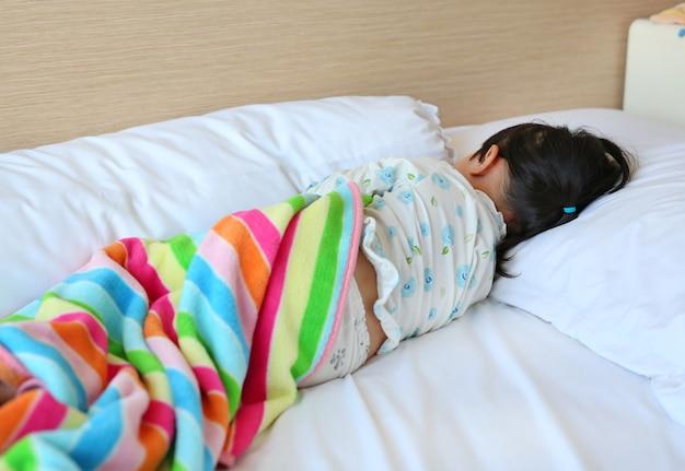 毛布でベッドで眠っているパジャマの少女
