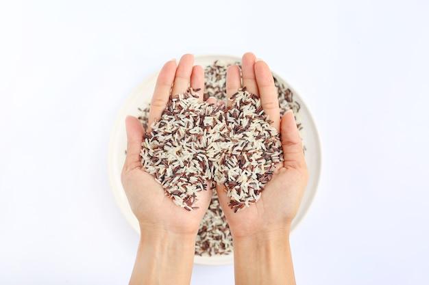 白い背景に白いプレートにジャスミン赤と白の米を持って手
