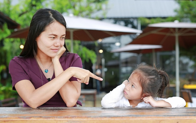 テーブル上で彼女の娘に叱る母親の肖像画。