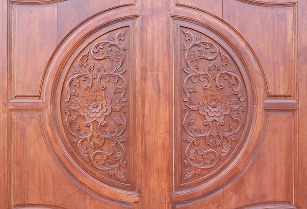 木の背景に彫られた花のパターン。伝統的な木製のタイスタイル