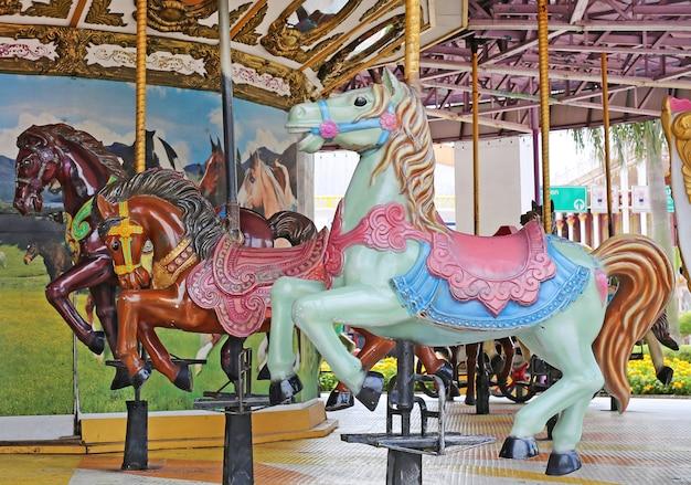 遊び場のヴィンテージスタイルの馬のカルーセル