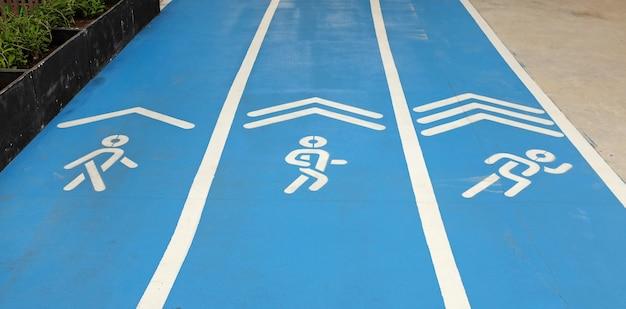 サイン、ウォーキング、ジョギング、走ることができる青色のスポーツランニングトラック