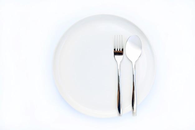 Вид сверху пустой блюдо с ложкой и вилкой на белом фоне