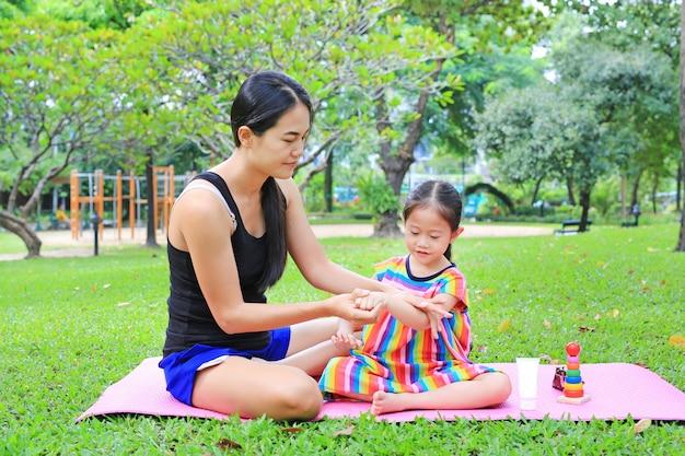 夏の公園にいる娘のためのマザーアピーニングボディーローション。