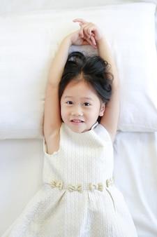 ハッピー美しいアジアの子供の女の子がベッドに横たわっています上から見る。