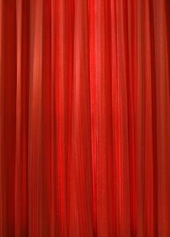 赤いカーテンの布の背景のテクスチャ
