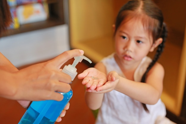 子供の手に洗浄ゲルを塗っている母親。