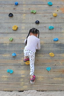 遊び場の木製の壁に屋外で自由に登ってみる小さな子供の女の子。