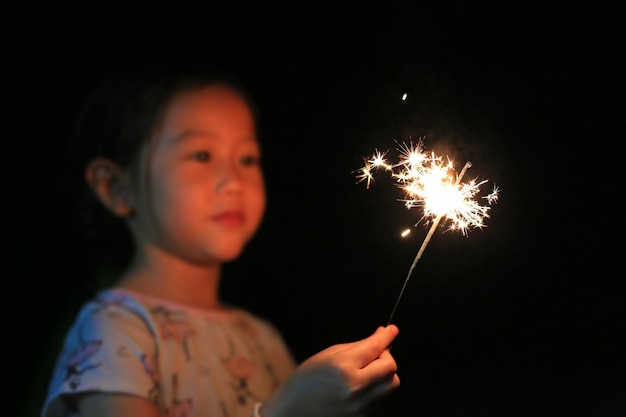 Маленькая азиатская девушка играя бенгальские огни огня в темноте.