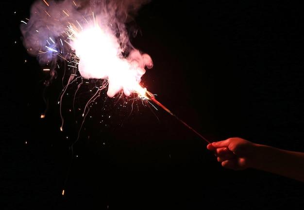Рука ребенка конца-вверх держа бенгальские огни огня на темноте на фестивале.