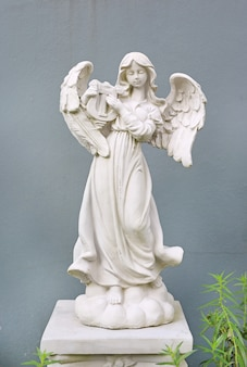 灰色の壁の背景に美しい天使の像。