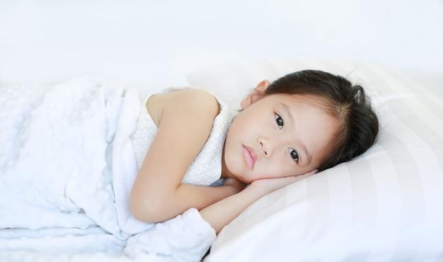 愛らしい美しいアジアの子供の女の子は、カメラを見てベッドに横たわっています。
