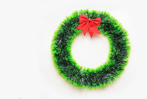 白い背景に赤いリボンとクリスマスの円形の花輪。