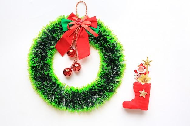 白い背景に赤いブーツと小さなサンタとクリスマスラウンドの花輪。
