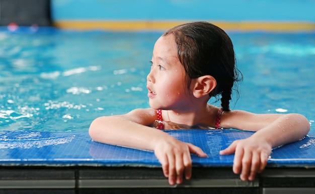プールで泳ぐことを学ぶ幸せな小さなアジアの子供の女の子の肖像画。クローズアップショート。