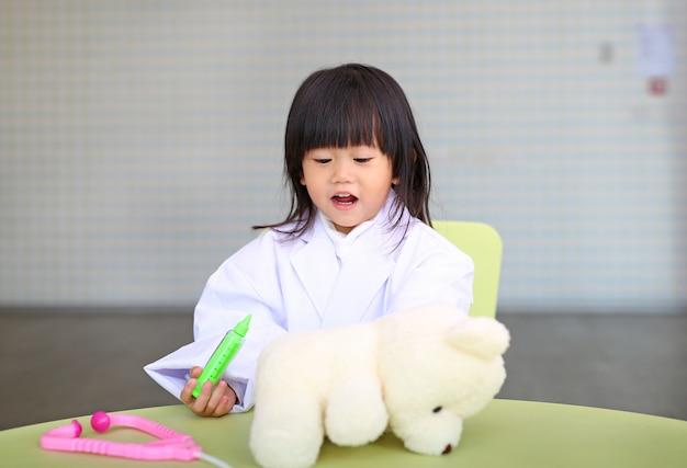 Милая маленькая девочка играет доктора