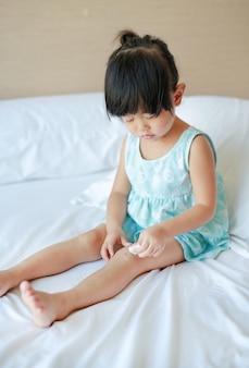 Закройте вверх девушки одевая рану на колене самостоятельно на кровати.