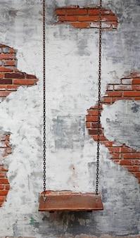 古いレンガ壁の背景に対して空のチェーンスイング