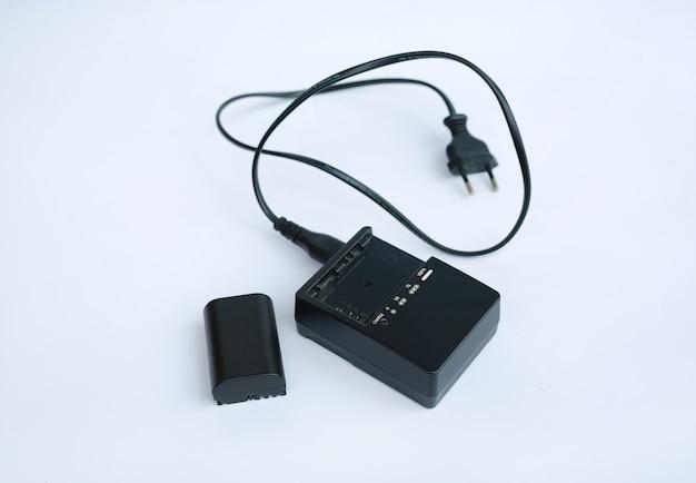 白い背景の上のバッテリーと充電器