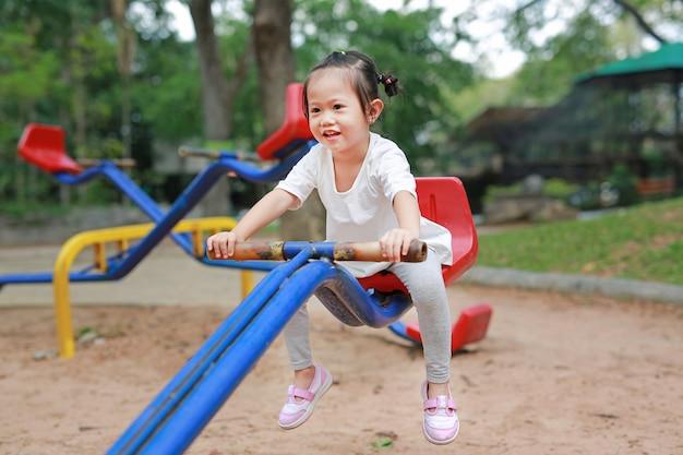 公園でのこぎりで幸せなかわいい女の子