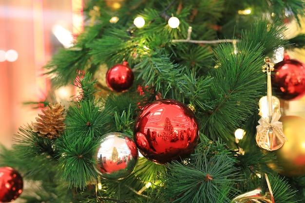 クリスマスボールと松の木の枝にぶら下がっている光。クリスマス冬の背景。