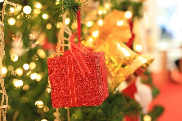 クリスマスの背景のための光でクリスマスの装飾品。赤いギフトボックスと松の木。