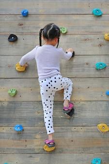 屋外の遊び場の木製の壁に無料で登山しようとしている小さな子女の子
