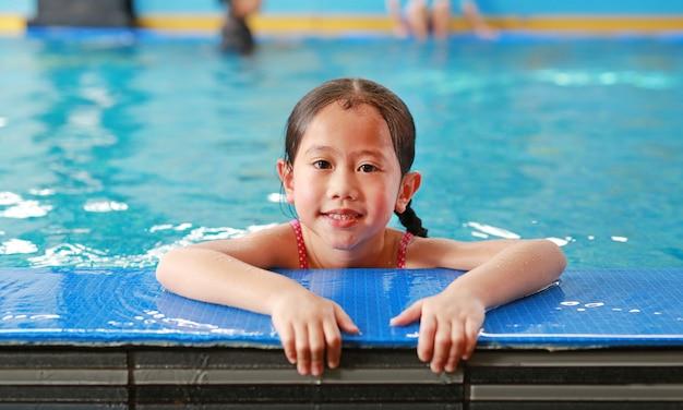 プールで泳ぐことを学んで幸せな小さなアジア子供女の子の肖像画。クローズアップ