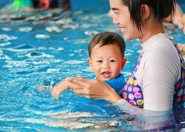 スイミングプールで男の赤ちゃんを教えるママの幸せな家庭