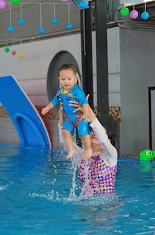 スイミングプールで赤ちゃんを教える母親の家族。