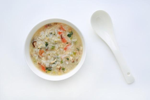 Каша для детского питания в белый керамический шар и ложка на белом фоне.