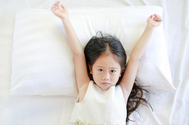 ベッドに横になっている美しいアジアの子供女の子の肖像画。上からの眺め。