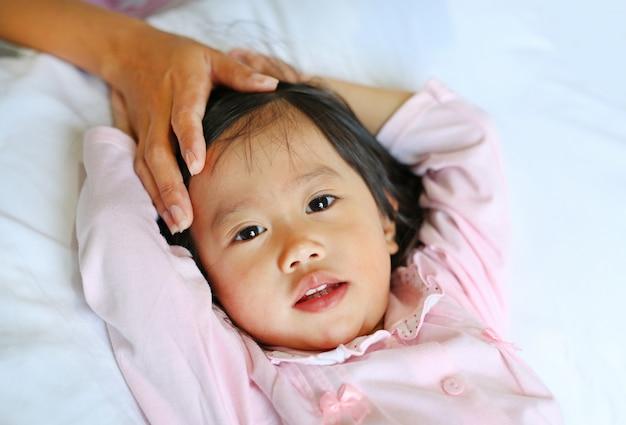 母親の手でベッドに横たわっている病気の女の子は、温度をチェックするために彼女の娘の頭に触れます。