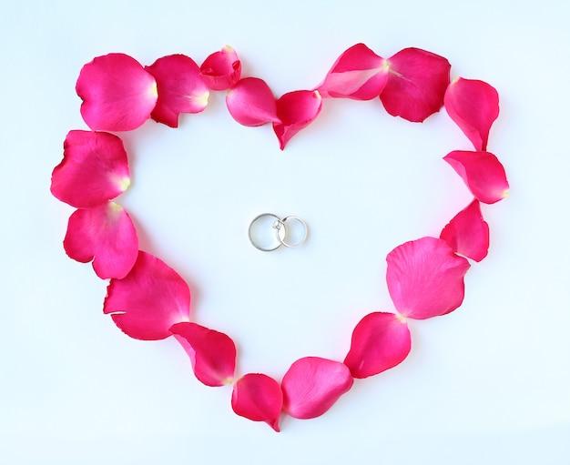 Лепестки розового цветка в форме сердца с пара обручальные кольца, изолированные на белом фоне.