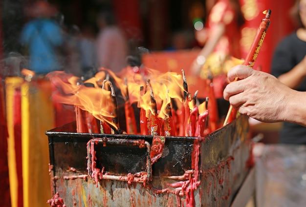 Люди молятся уважением с зажженной свечой для бога в китайский новый год.