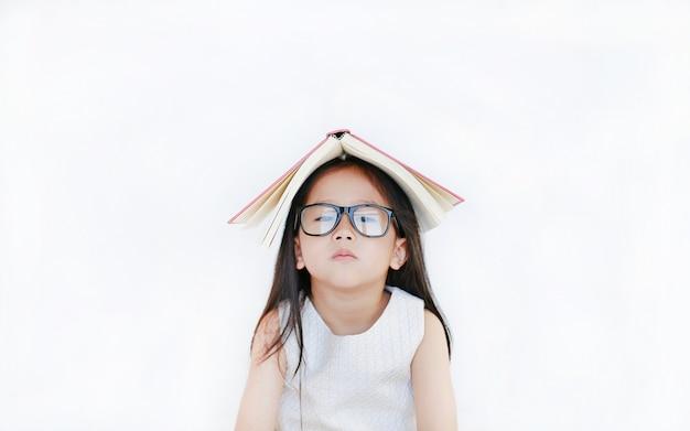 小さなアジアの女の子の肖像画は彼女の頭の上のハードカバーの本を置き、白い背景の上にカメラを探しています。