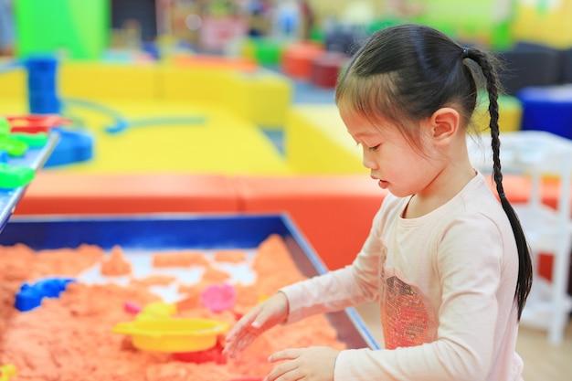Азиатская девушка малыша играя кинетический песок.