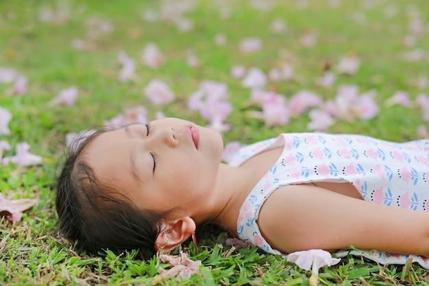 屋外の庭で秋のピンクの花と緑の芝生で寝ているかわいい女の子。