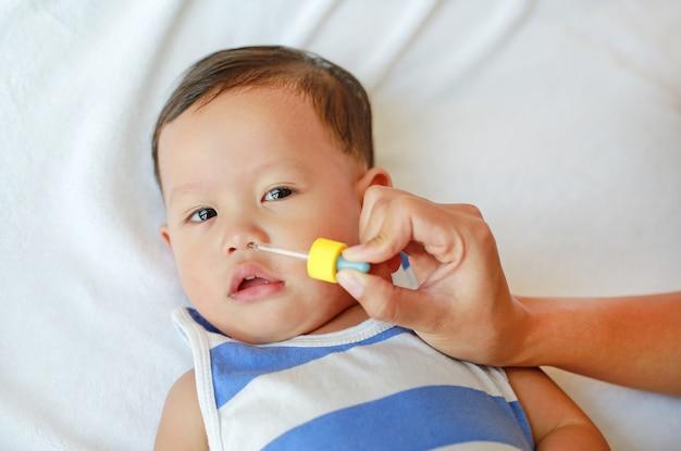 アジアの男の子は点鼻薬を飲みます。ベビーケアのコンセプトです。
