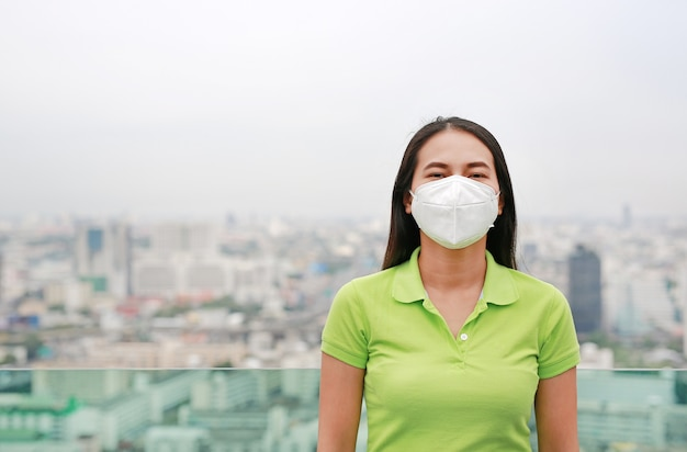 バンコク市内の大気汚染に対する保護マスクを身に着けている若いアジア女性。
