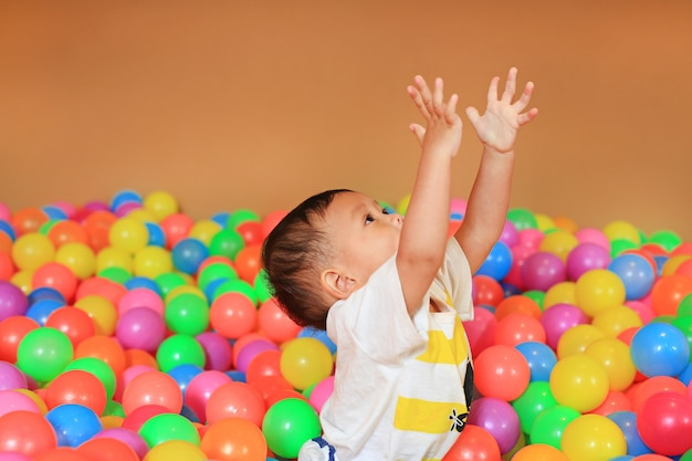 カラフルなプラスチック製のボール遊び場で遊ぶ男の子の赤ちゃん。