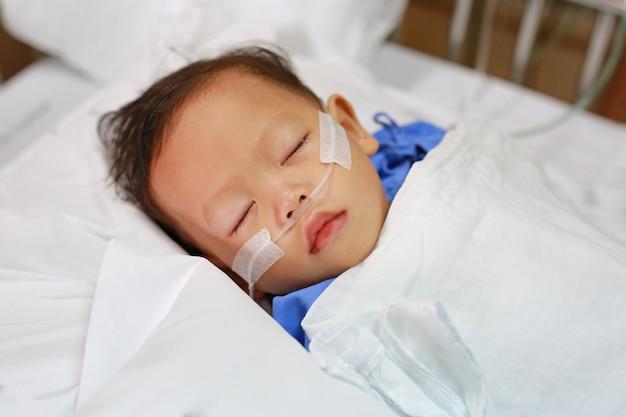 治療を受ける鼻の中の呼吸管を持つ男の子。病院での集中治療