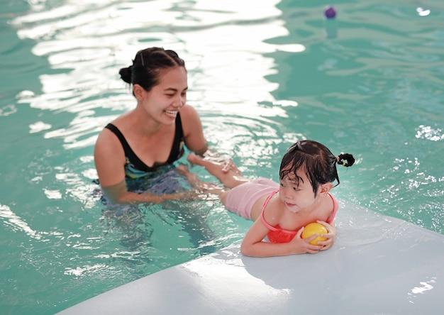 スイミングプールのトレーニングで赤ちゃんと母親
