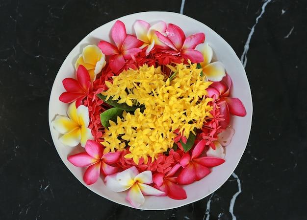 黒い大理石の背景に白い皿に咲く花の上から見たスパのコンセプト