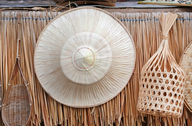 わらの壁の背景にタイの伝統的な農家工芸品帽子がハングします。