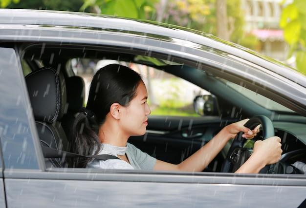 若いアジア女性が雨が降っている間車を運転します。
