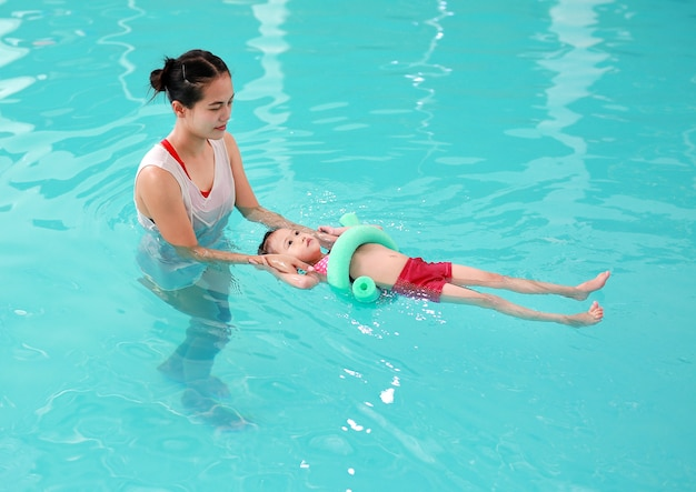泡麺付きのスイミングプールで子供を教える母