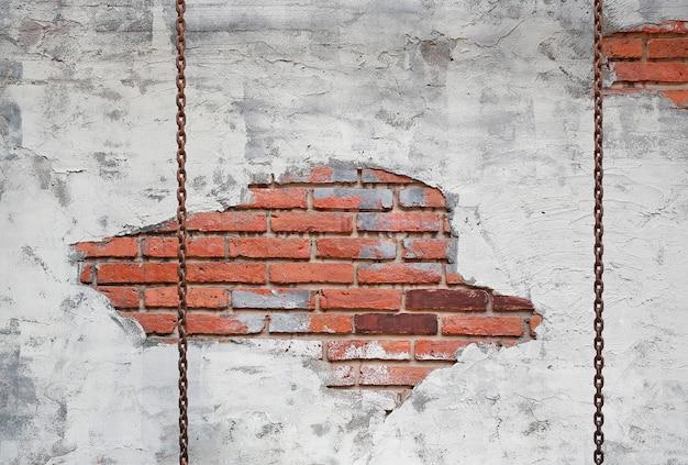 古いレンガ壁の背景に対してチェーンスイング