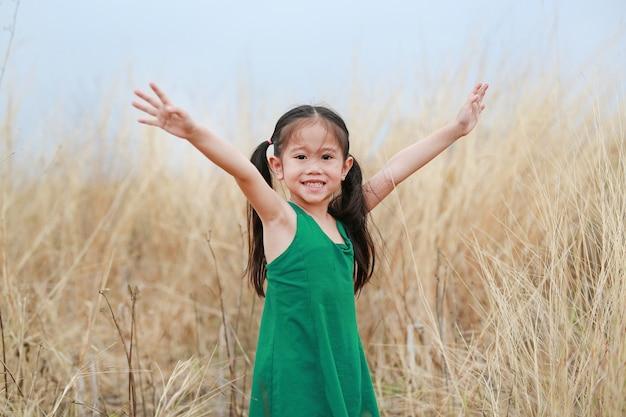 乾いた芝生のフィールドで両手を広げて愛らしい小さなアジア子供女の子。