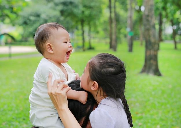 自然公園で妹と遊んでママの肩に乗って幸せな男の子。